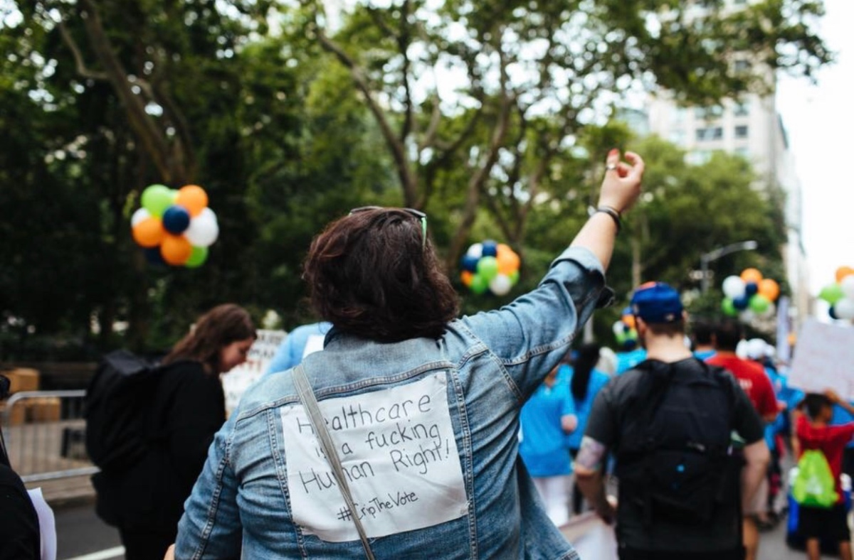 "A photo of Ali at the NYC Disability Pride Parade. She is faced away front the camera and is wearing a jean jacket with a grey sign pinned on the back. ""Healthcare is a fucking Human Right! #CripTheVote"" is written in black sharpie. Her arm is raised in the air and her hair is pulled off to the side. The are trees, balloons, and others people participating in the parade around her."
