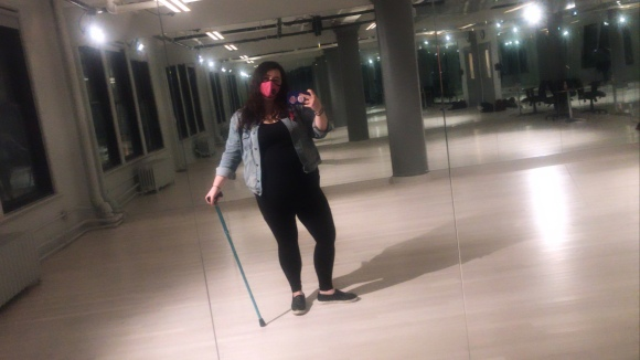 A mirror selfie of Ali in a dance studio. She is wearing all back and a jean jacket. Her hair is long, curly, dark. She also has a bright pink face mask on and a teal cane in her hand.