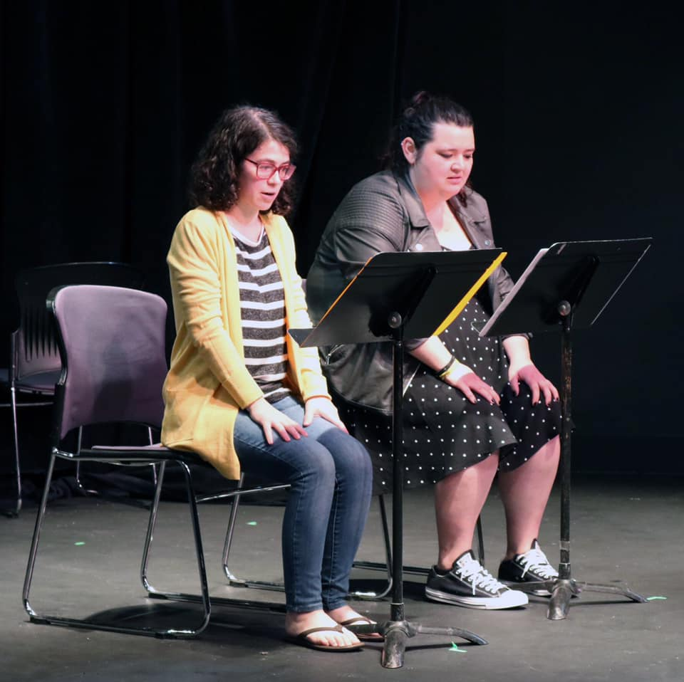 A photo of a staged reading at Queens Theater. Ali, who is wearing a black and white poka dot dress, a grey leather jacket, and her hair pulled up into a ponytail is sitting on the right side of the stage. Next to Ali is her scene partner, Nicole, who is wearing a yellow cardigan, black and white striped shirt, jeans, glasses, and short, dark, curly hair. There is a music stand in front of both girls and they are sitting in the same shape with their hands flat on their thighs. Behind them is the black box theater.