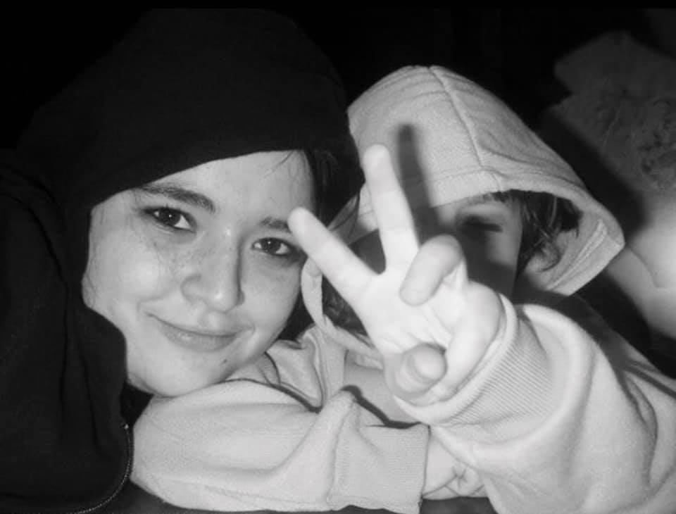 A photo of Ali and her little sister from about 9 years ago. Ali is wearing a black sweatshirt with the hood up and is resting her head on her sister's shoulder. Her sister is wearing a pink sweatshirt and has the hood up and has her hand in front of her face making a peace sign.