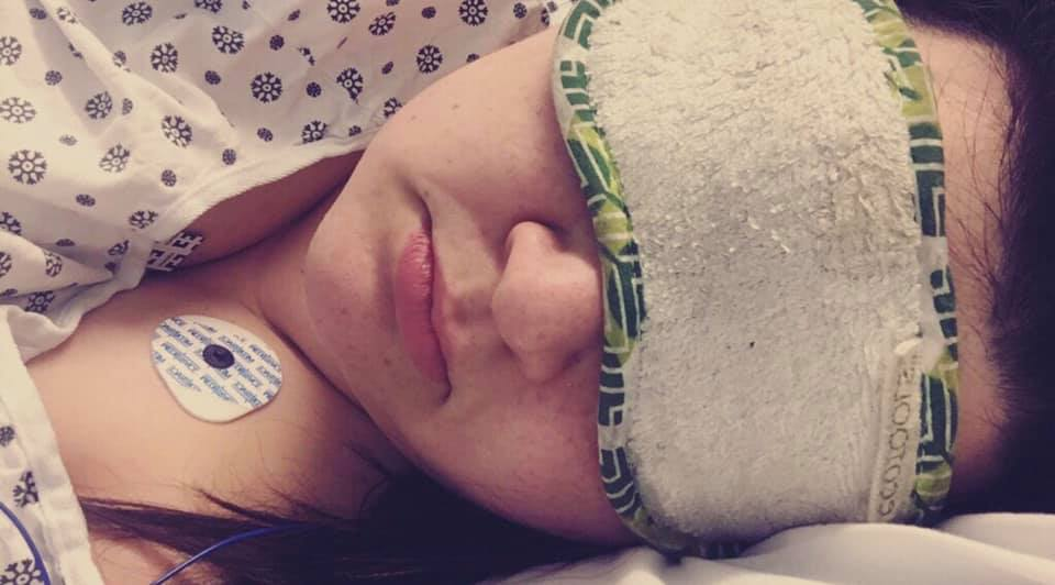 A photo of Ali lying on her side. She is wearing a hospital gown, leads for an EKG, and an eye mask.
