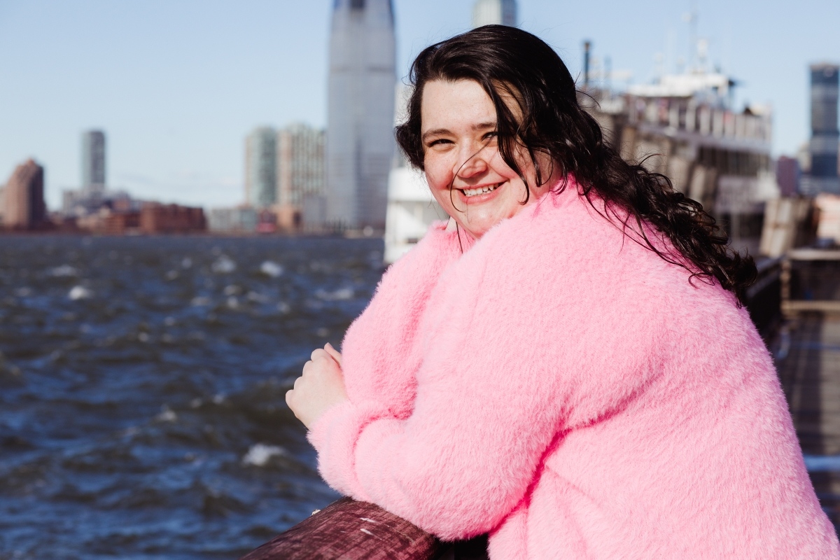A photo of Ali looking over the pier at Battery Park. Her hair is blowing in the wind and she is smiling towards the camera.