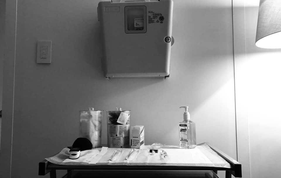 A black and white photo of a tray with medical supplies on it.